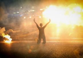 A woman kneels in the street as tear gas rains down. (CC licensed).