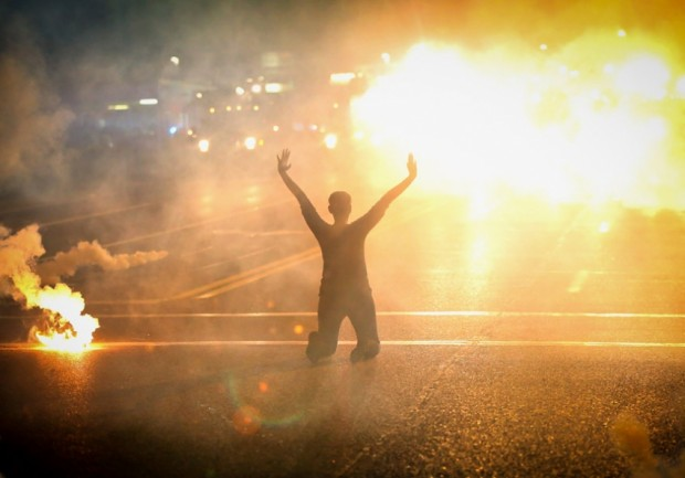 A woman kneels in the street as tear gas rains down. (CC licensed).